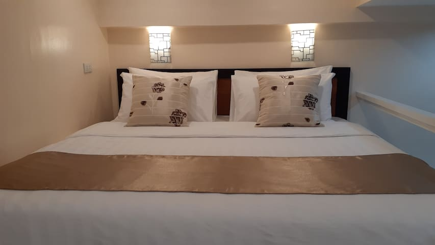 Bed is custom-sized to 72 inch by 75 inch and can fit 3 adults. Furnished with crisp and clean white linen, this probably one of the best bed you've ever slept.