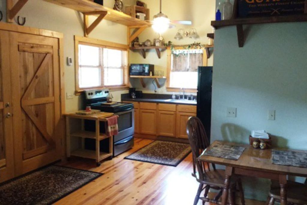 Dining, cooking, and an efficient kitchen area with full size refrigerator for use.