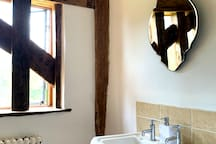 The vintage beams add depth of character to the traditional bathroom