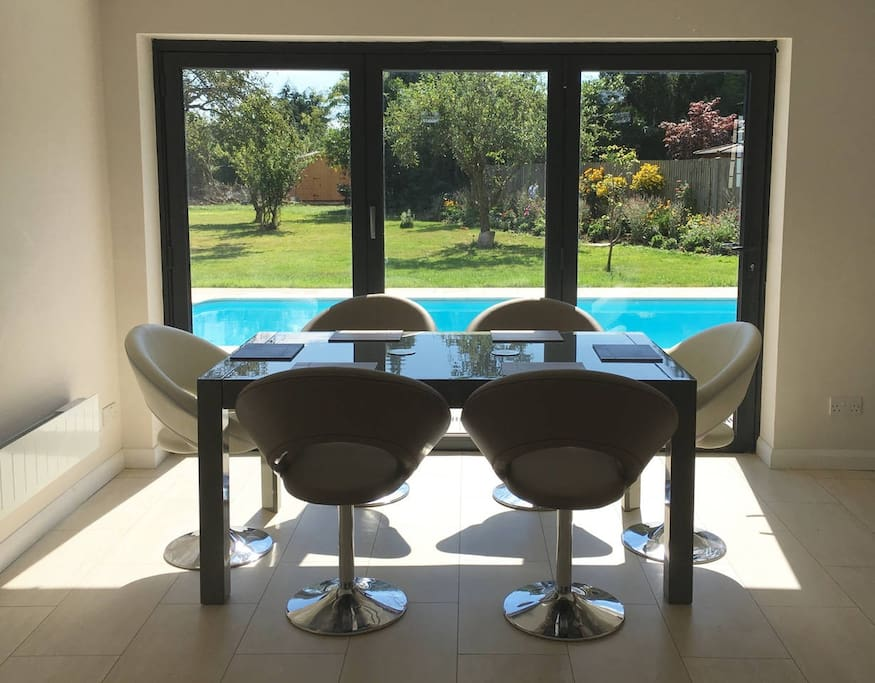 Dining table overlooking pool and gardens with bi fold doors
