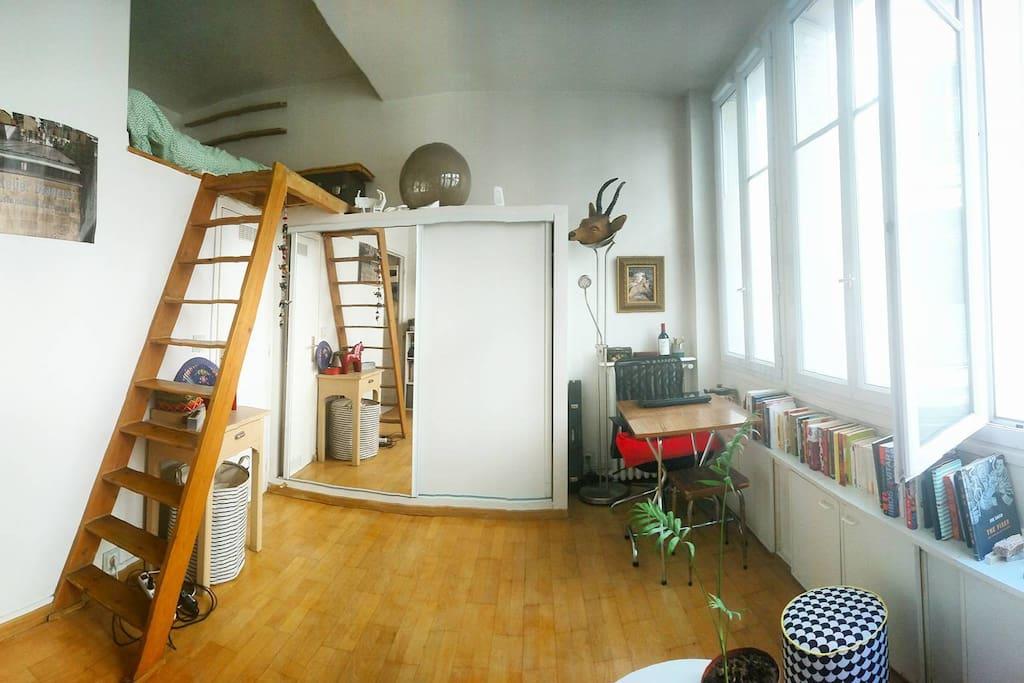 Espace de travail/sale à manger, des chaise supplémentaires pliantes en bois se trouvent sous le sofa. La sale de bain se trouve sous la mezzanine.