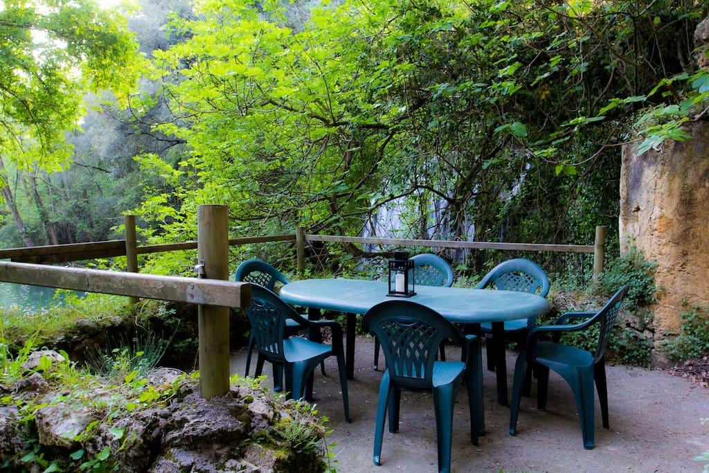 Mesa en el jardín vista al lago y a la cascada