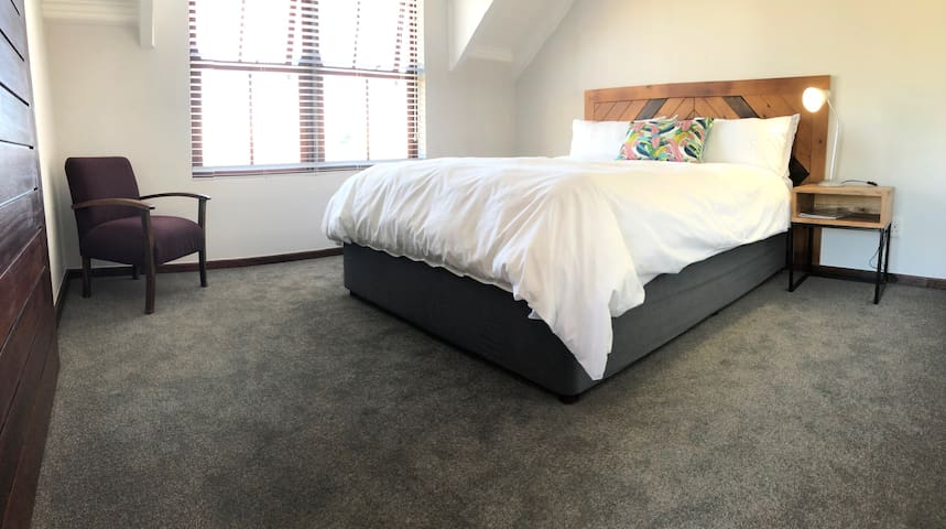 Master bedroom which includes a Queen size bed, comfy chair, bed side tables and headboard.