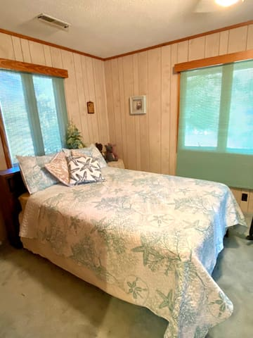 """""""Shell Room""""— double bedroom decorated in sea glass blue. Room furniture includes chest-of-drawers, dressing table, mirror, closet, and sitting chair."""