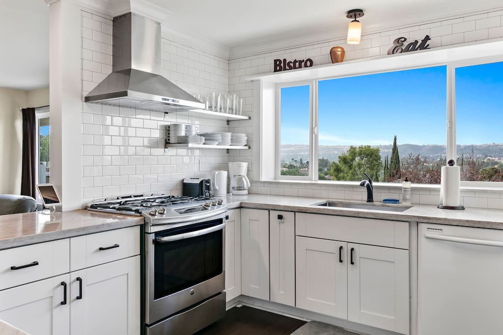 White subway tile and a stainless gas range are on display next to a massive window overlooking California hilltops.