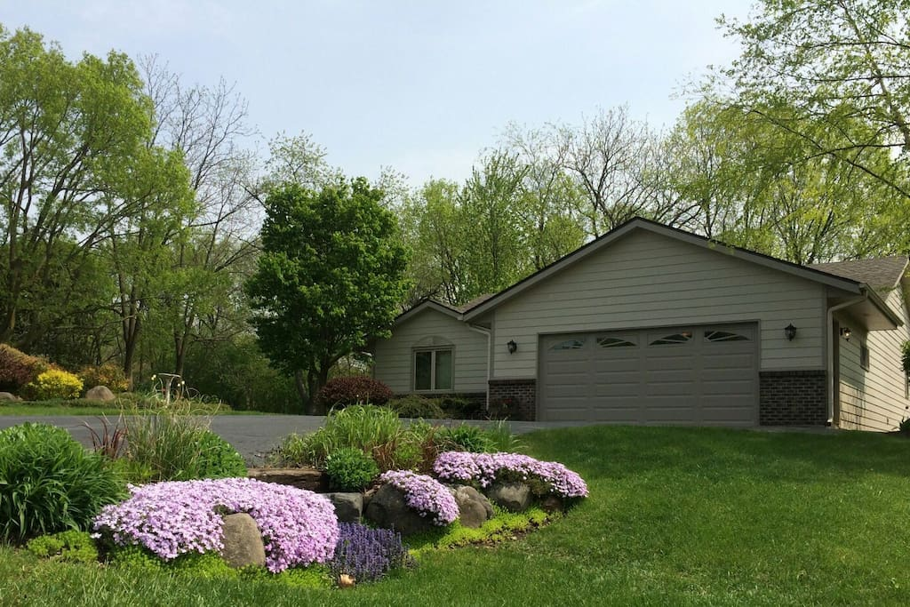 Street view, spring, ample parking in driveway. Boulder landscaping, river birch tree, lilac tree