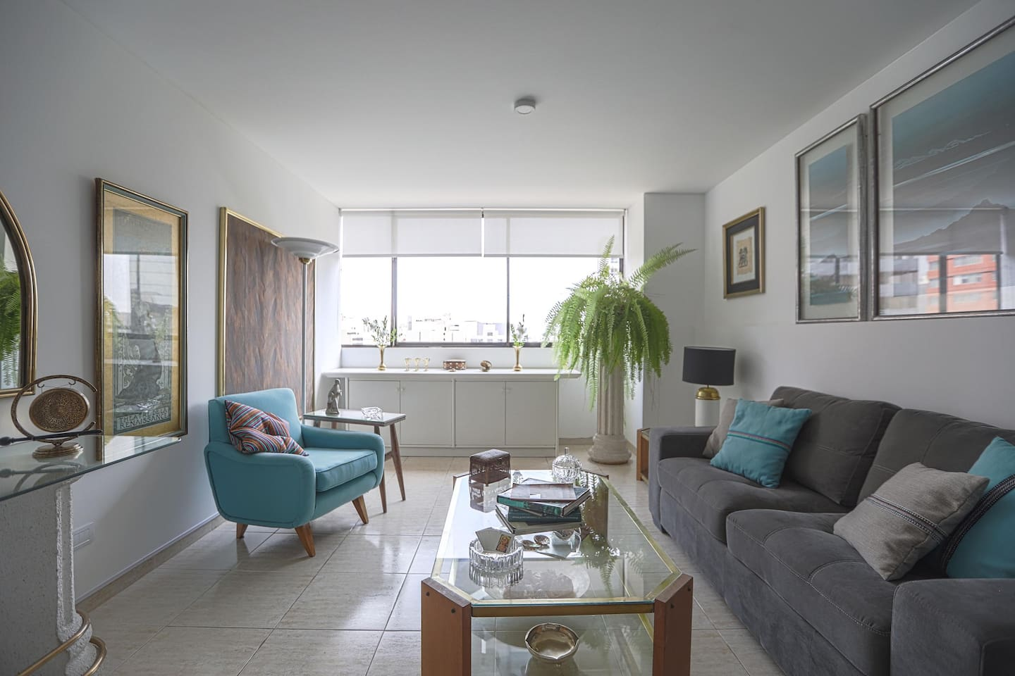 Living room. You can see the boulevard through the window, full with trees, benches where people take a rest, use their bikes along it, walk their dogs and so on. To the right is the sofa that turns into a double bed.
