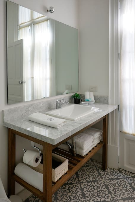 Baño completo con amenidades como shampoo, acondicionador, crema hidratante, secadora de pelo, bata y pantuflas.
