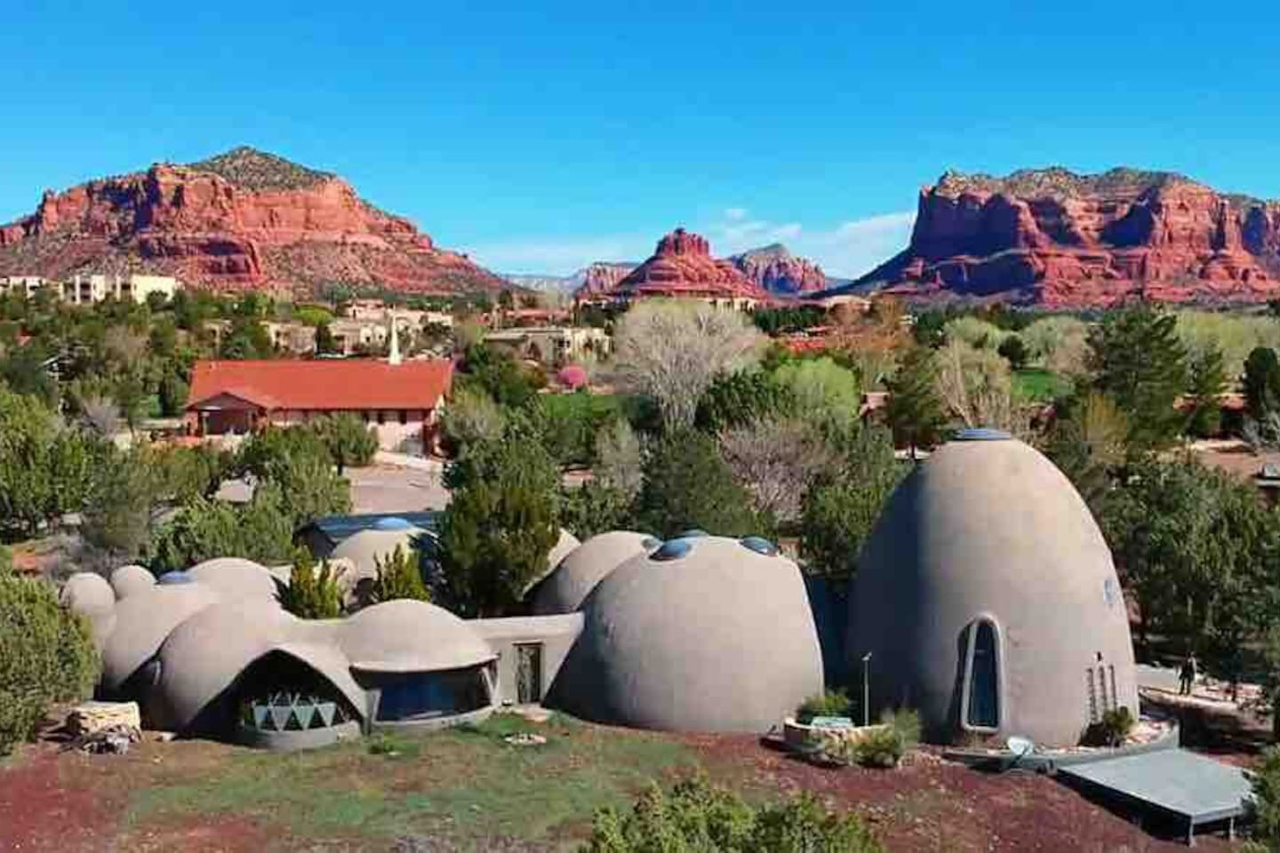 Drone view of the Sedona Domes' ten domes in a ring with the  Bell Rock Vortex in middle background, Castle Rock to the left and Courthouse Butte to the right.