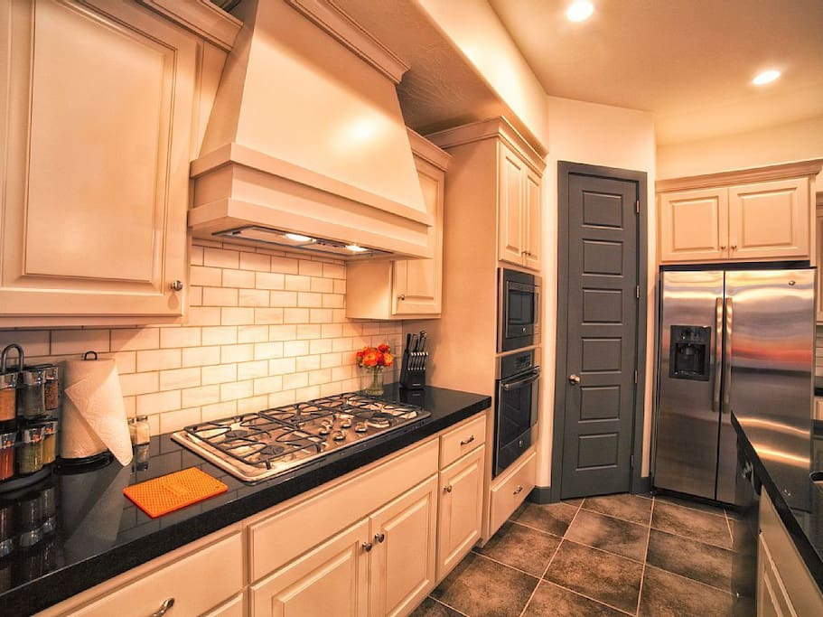 Kitchen includes stove, oven, utensils, appliances, dishwasher, toaster, microwave