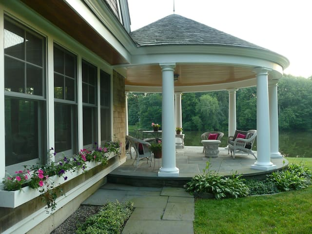 Lush gardens, flower boxes and covered round porch.