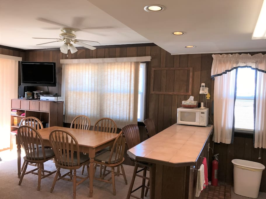 Large table with 6 chairs, stools at countertop