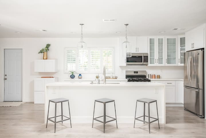 Open kitchen with beautiful island, GREAT for entertaining and cooking with big groups. Pots, pans, dishes, baking dishes, Tupperware, foil,  Ziplocs, basic cooking items provided!