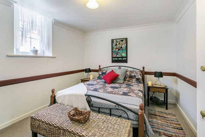 BEDROOM 1 is located downstairs & offers a queen bed, hanging hooks behind the door, ceiling fan & oil heater.