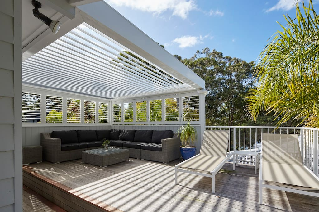 Relax on the upstairs undercover sundeck with outdoor sofa and sun loungers.