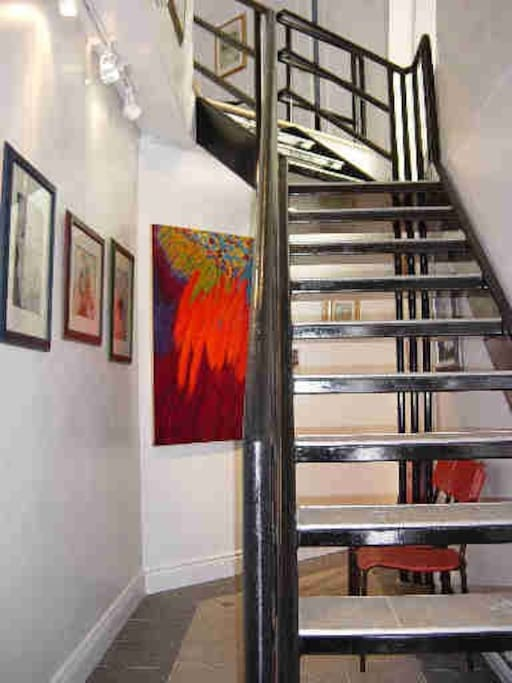 Vertical Gallery of Art in Entry and indoor staircase to Studio Loft