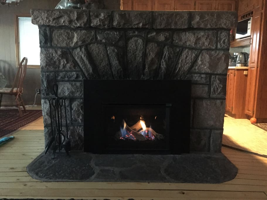 The original stone fireplace circa 1940 with a gas insert installed in 2017. A glimpse of the kitchen and dining area in the open-plan main floor of the cottage.