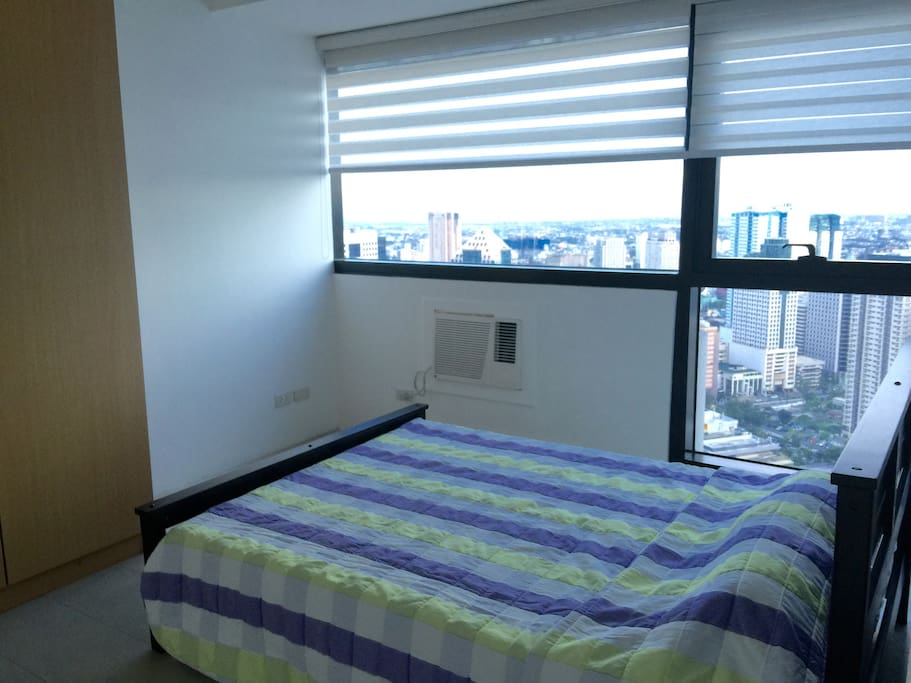 Separate bedroom with queen size bed with a view overlooking Ortigas CBD