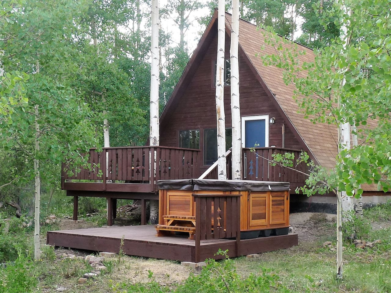 A view of the back deck of our cozy cabin.  Enjoy dinner and drinks on the deck then relax under the stars in the hot tub.