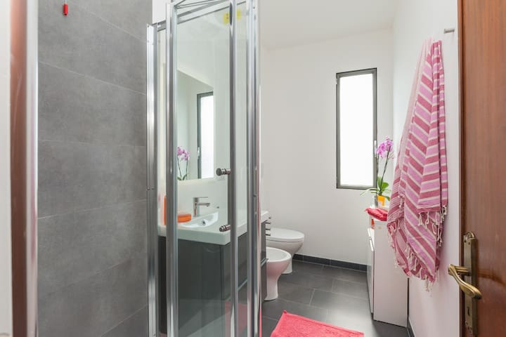 the bigger bathroom comes with shower cabin, toilet, bidet, sink with 2 drawers and another cabinet under the window