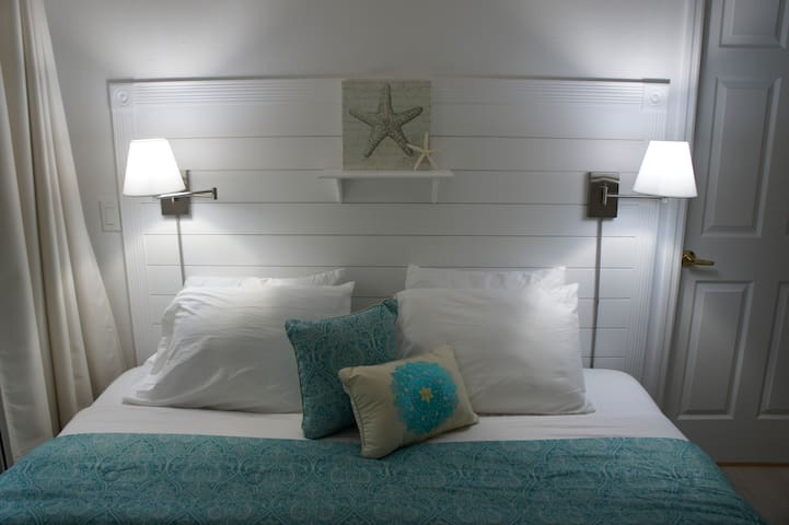 King size bed, newly installed ship lap headboard with wall mounted swing arm night lights for reading your favorite vacation book
