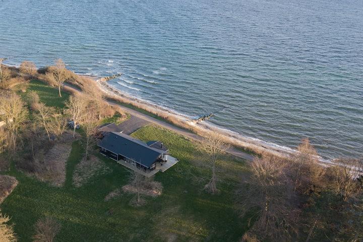 Nyt sommerhus med privat strand og skov