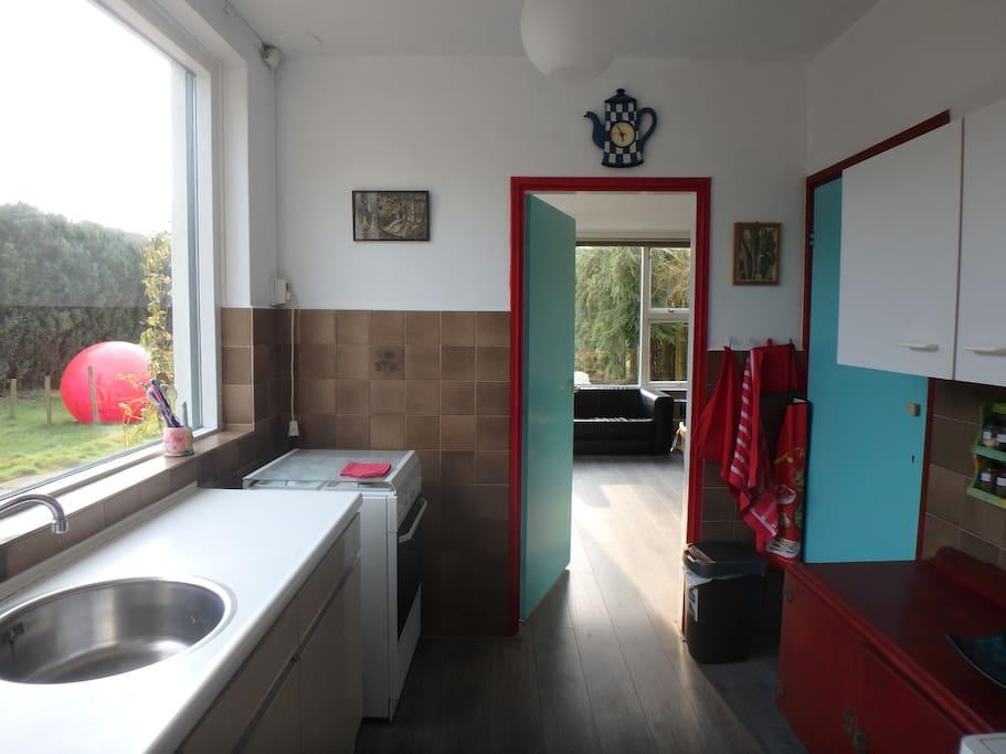 Keuken met zicht op woonkamer en wat tuin