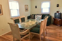 """Dining room is 10""""x 17"""" Table seats 6 or 8. The green comfy couch in the back is great for one person to sleep on."""