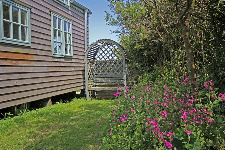 The tiny house garden complete with arbour and wild flowers
