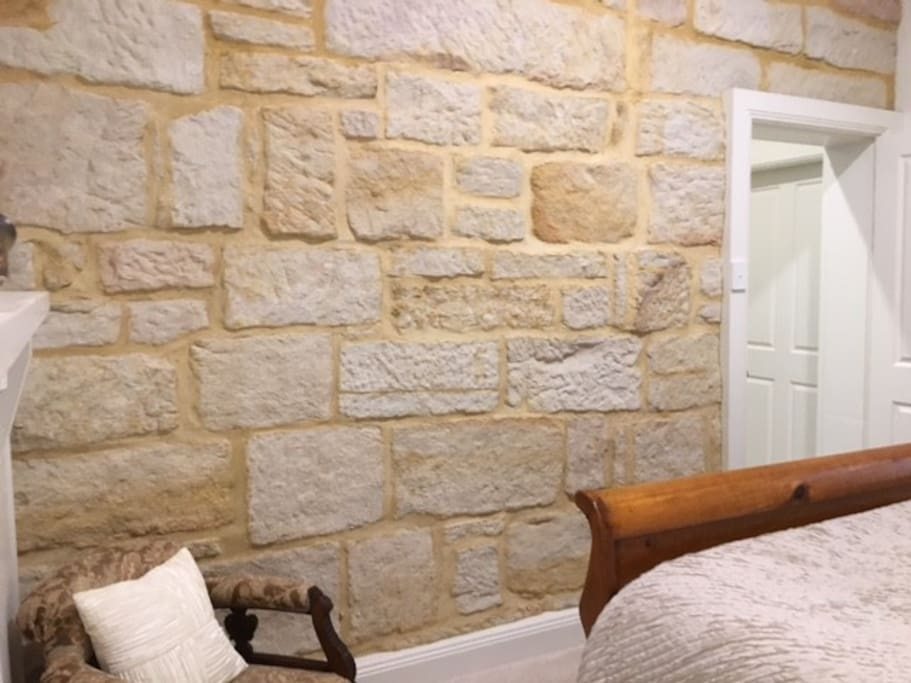 Queen bedroom with featured sand stone wall.