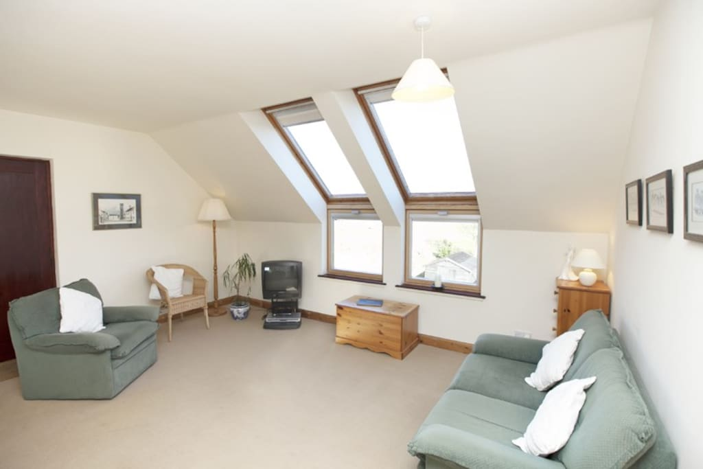 Living area with windows overlooking rear garden and river estuary