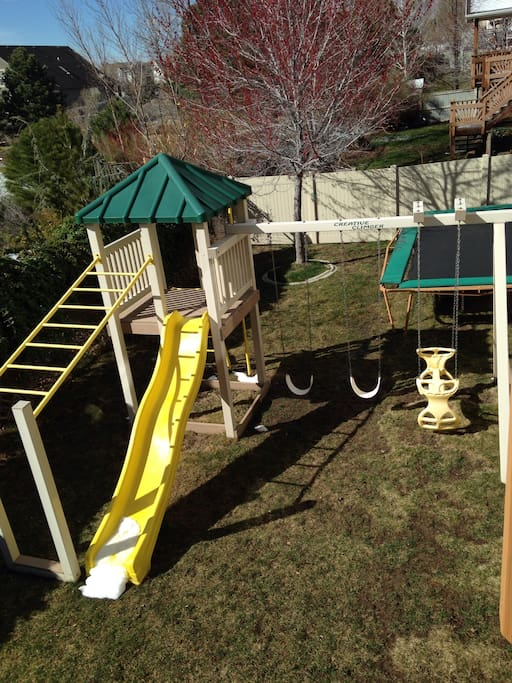 Swing set and trampoline in backyard.