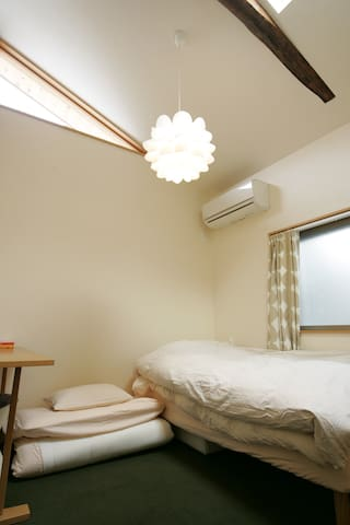 Small but cozy guest room upstairs has a single bed, a set of futon and a writing desk.