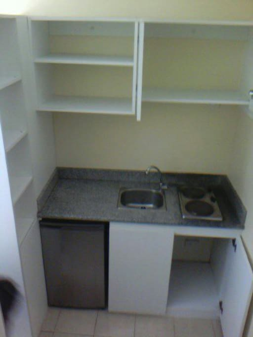 Kitchen has double burner electric stove, refrigerator, cupboards