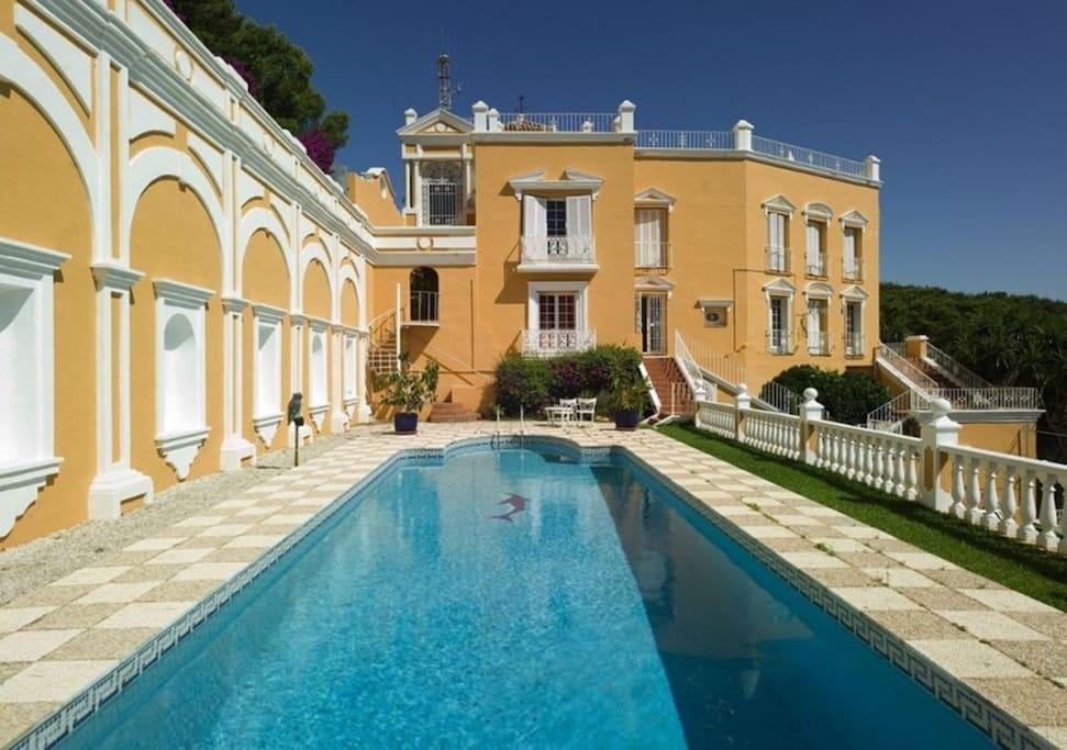 very large swimming pool with large terrace with lounge sets