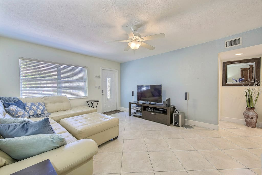 """The living room is furnished with an upscale white leather sectional and ottoman. Sink into ocean-blue pillows and watch your favorite films on the 52"""" flat-screen TV."""