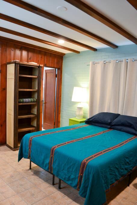 Queen bed with door to bathroom