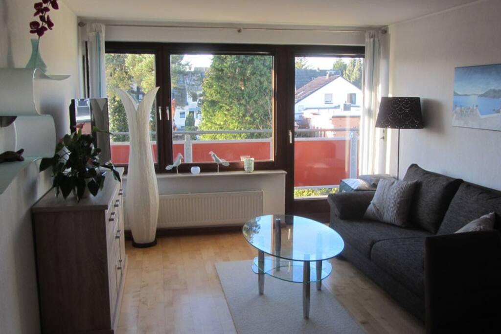 Wohnzimmer Sitzecke und Blick auf den Balkon rechts davon grosse Dachterasse