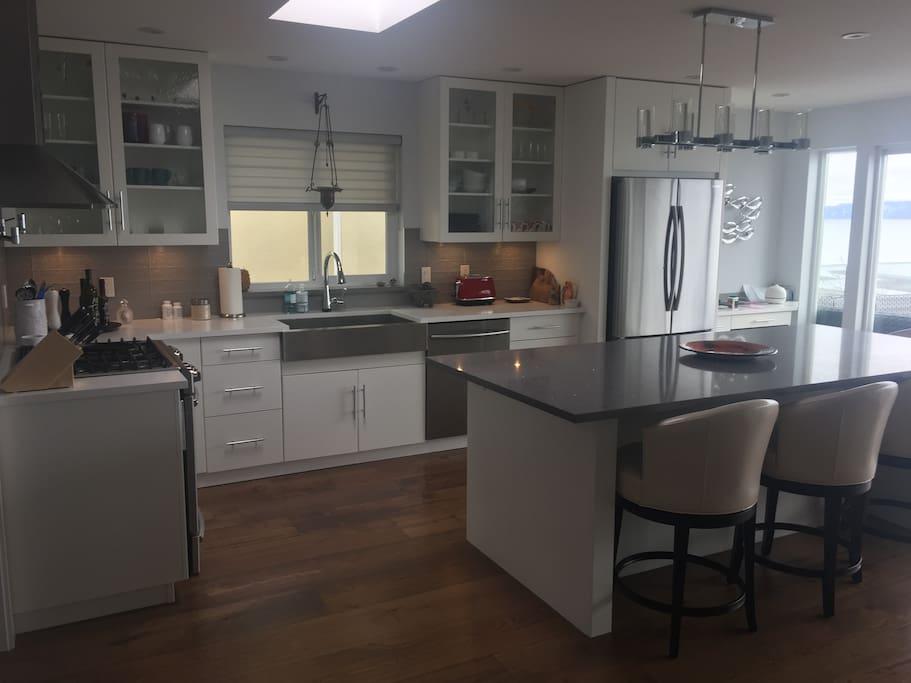 Fully stocked, modern kitchen with 5 burner gas stove, Dishwasher and large fridge.