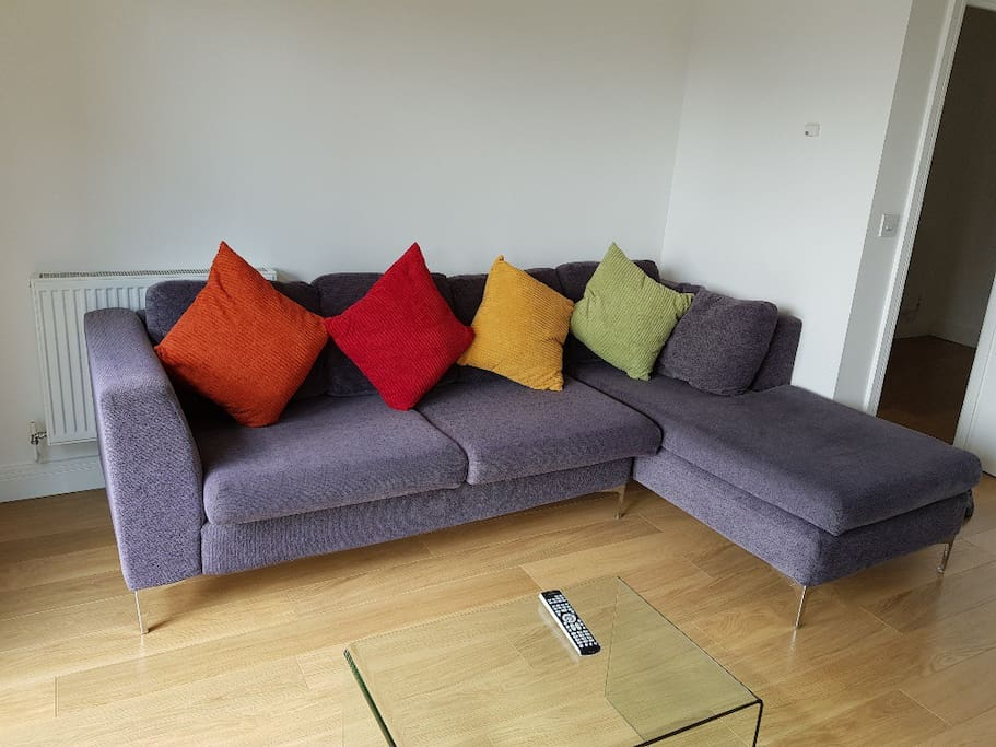 living room with a long sofa that stretches that can be use as a bed