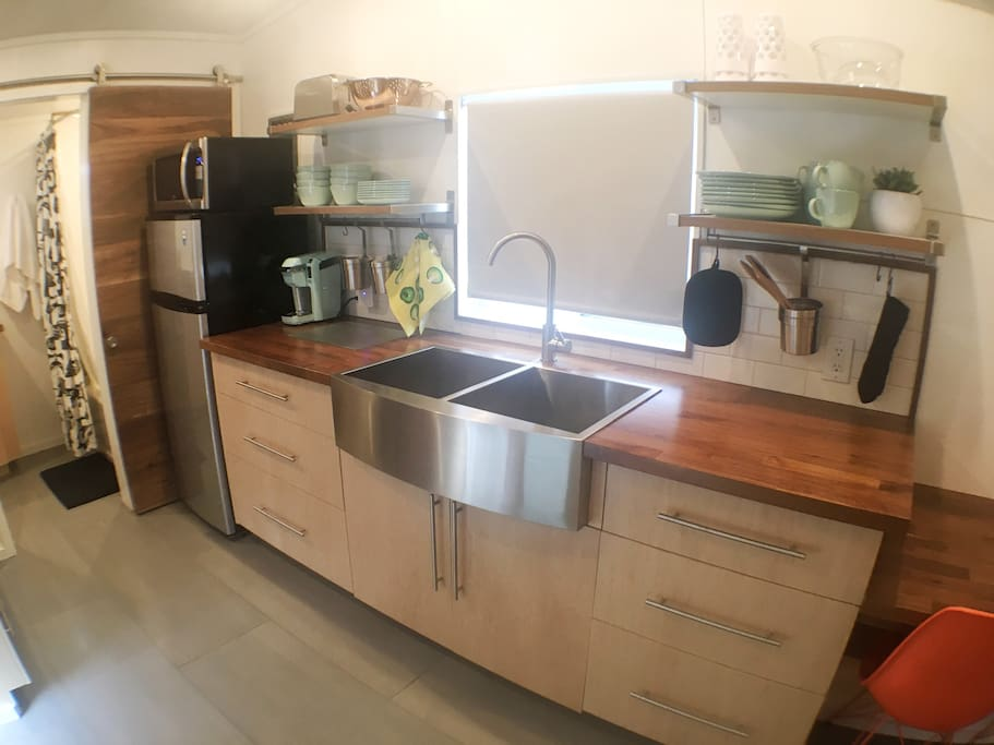 Small, but concise kitchenette with all the essentials. Fridge, microwave, Keurig coffee machine and coffee. Plates, Bowls, Mugs, mixing bowls, toaster, cooking utensils.
