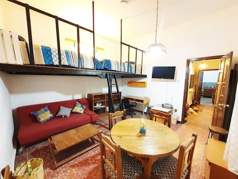 Habitación- estancia  con 2 camas individuales en tapanco asegurado con barandales y escalera fija para la mayor seguridad de los huéspedes. Escritorio, pantalla smart, comedor y sofá.
