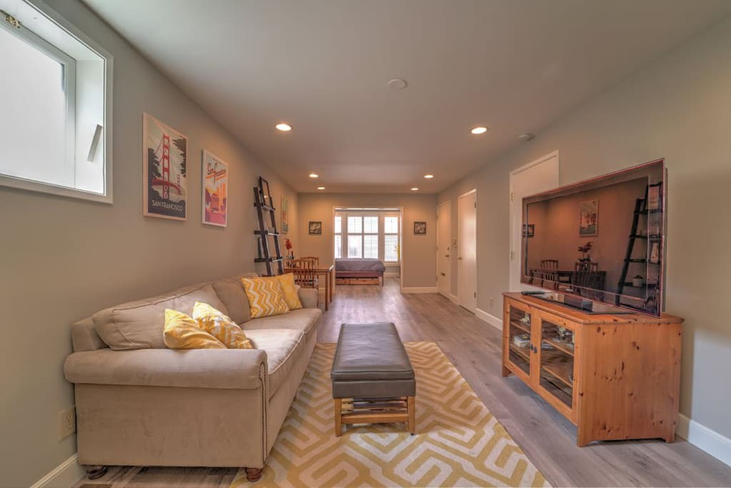 Large, light-filled living space with bedroom in distance. New hardwood floors throughout!