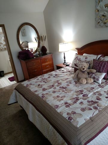 King size bed with dresser , nightstands and 55 inch TV with a full-sized private bathroom