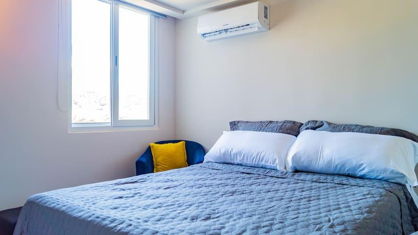 Habitación principal con aire acondicionado, cómoda cama queen y vista de la ciudad.  Master bedroom with air conditioning, comfortable queen bed-size and city view.