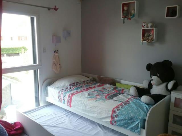 Chambre 1 de l'étage de plus de 11m2 avec un lit 90×200 et un lit d'appoint gigogne des mêmes dimensions
