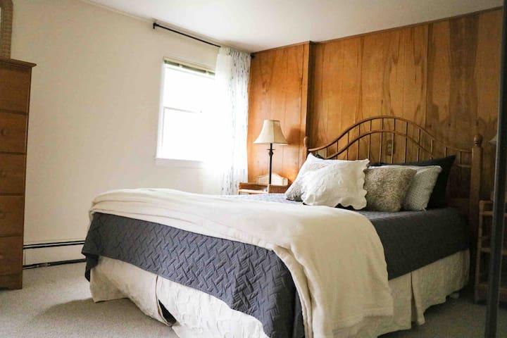 Cozy bedroom with a queen bed & a closet.