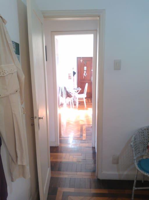 Entrada do quarto. Ao fundo a sala do apartamento.