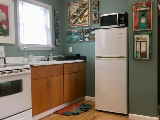 Full kitchen with half-sized fridge and a vintage farm sink.
