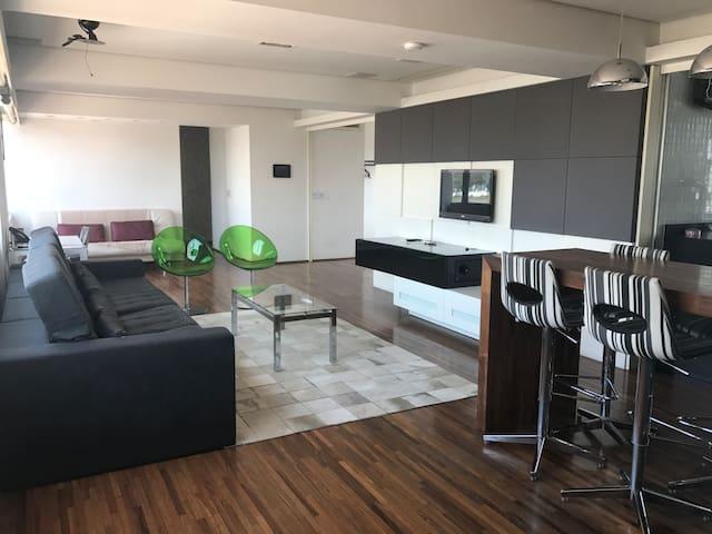 Ampla sala com TV, mesa com 6 lugares, sofá de 4 lugares, 2 cadeiras e mesa para notebook ao fundo